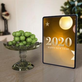 Mock-up tablet com mensagem de desejo de ano novo na mesa