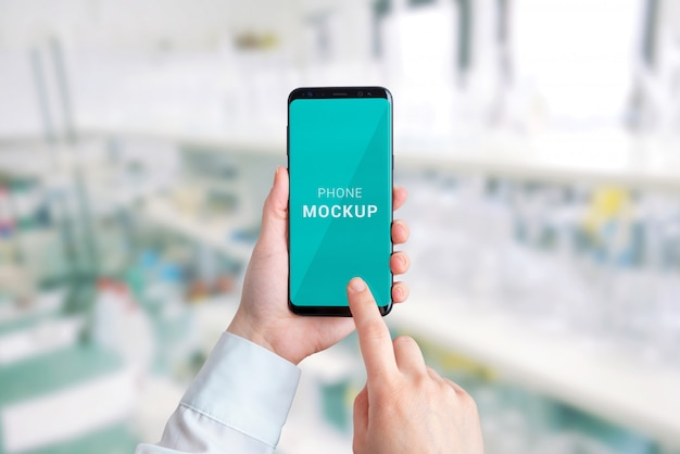 Mocku de telefone inteligente nas mãos. laboratório em segundo plano. conceito de apresentação de aplicativo de hospital