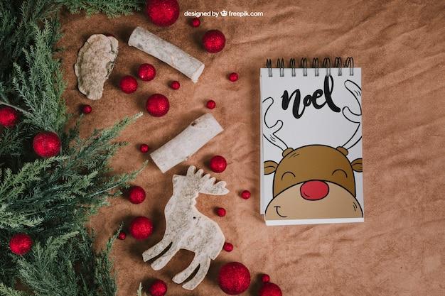Mockup de natal com bloco de anotações ao lado de bolas e renas