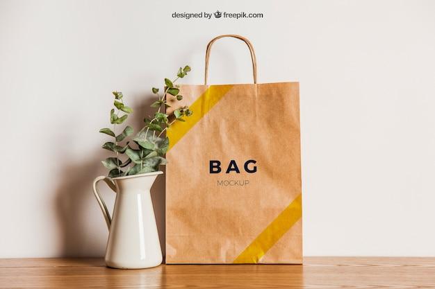 Mockup de saco de papel ao lado do vaso de flores