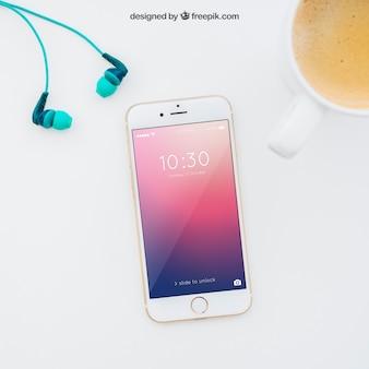 Mockup de smartphone com fones de ouvido e café