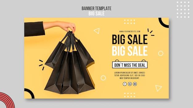 Modelo de banner horizontal para grande venda com mulher segurando sacolas de compras