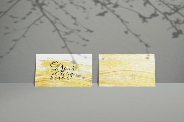 Modelo de cartão de visita em um fundo cinza com sombra de folhas