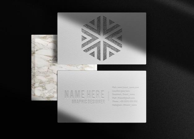 Modelo de cartão de visita luxuoso com logotipo em relevo preto e pódio de mármore