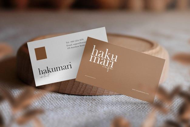 Modelo de cartão de visita mínimo limpo com madeira pequena placa na mesa e sombra clara.
