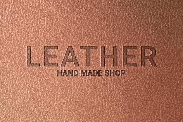 Modelo de logotipo em relevo psd para empresa em fundo de couro marrom
