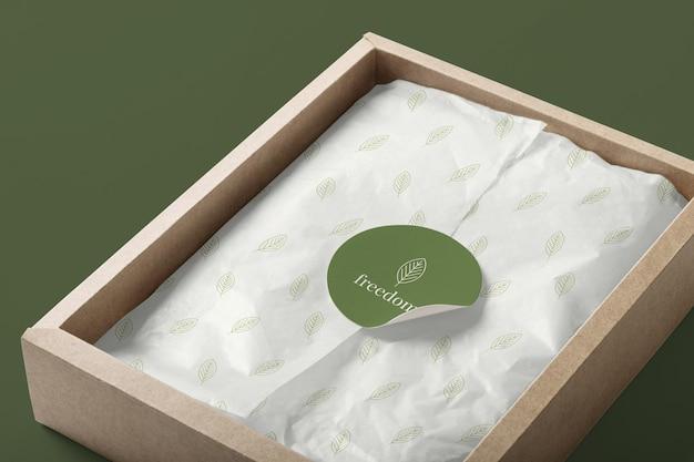 Modelo de maquete de adesivo de papel realista em uma caixa