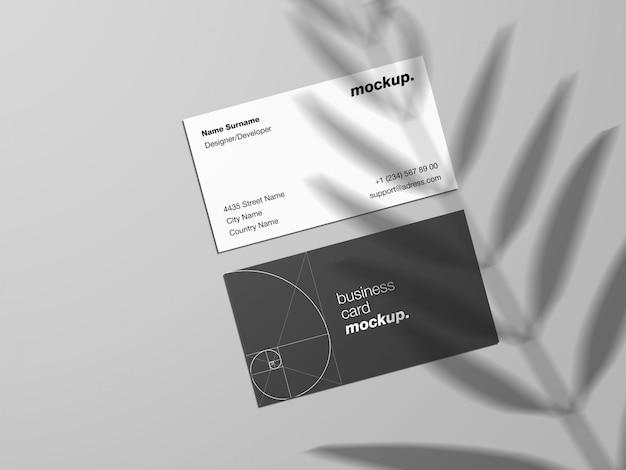 Modelo de maquete de cartões de visita com sobreposição de sombra em folha de palmeira