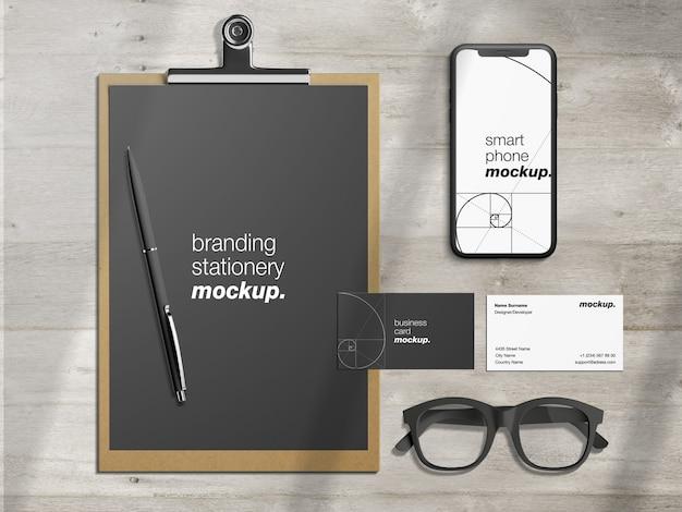 Modelo de maquete de identidade de marca corporativa profissional com papel timbrado, cartões de visita e smartphone na mesa de madeira