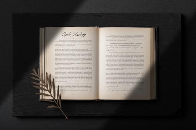 Modelo de maquete realista livro aberto com folhas secas