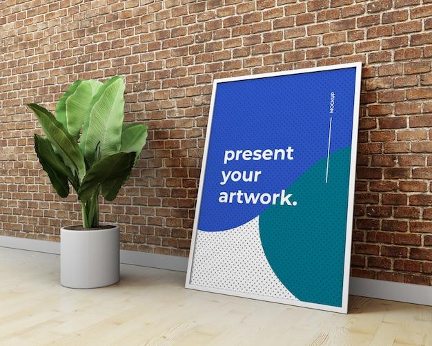 Modelo do cartaz / arte finala de psd na parede e na planta de tijolo. maquete do cartaz no interior