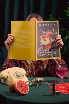 Modelo lendo uma revista de moda dentro de casa