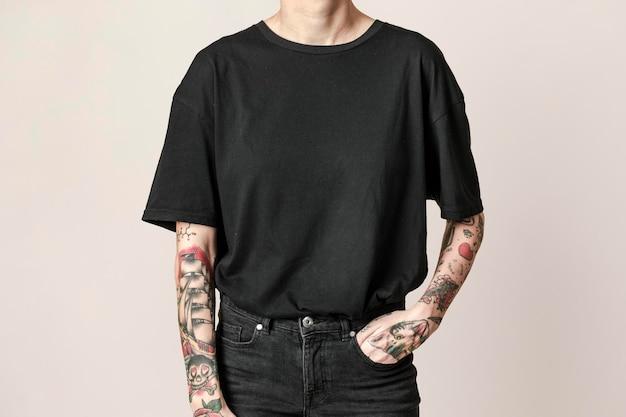 Modelo tatuado em camiseta preta e maquete psd de jeans