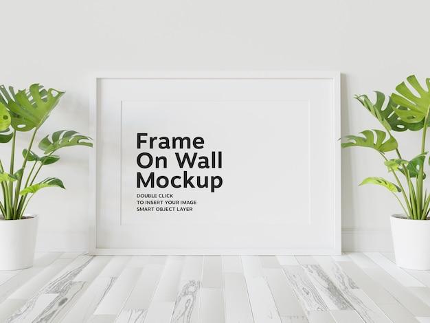 Moldura branca apoiada em maquete de parede