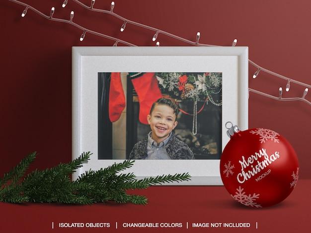 Moldura de cartão de foto de saudação de feriado e maquete de bola de natal e criador de cena