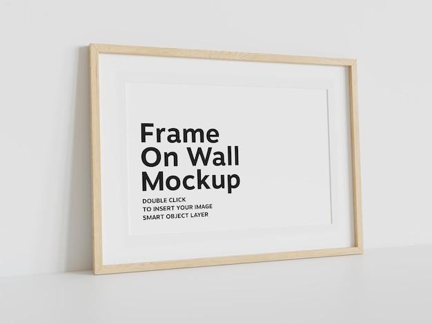 Moldura de madeira apoiada em maquete de parede branca