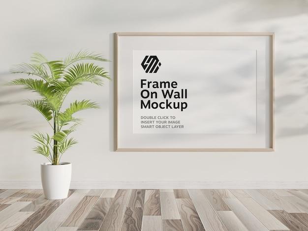 Moldura de madeira pendurada na maquete de parede