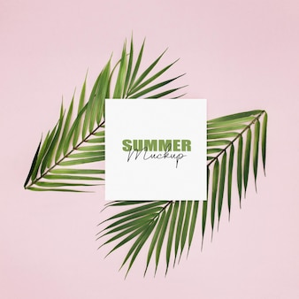 Moldura de maquete com folhas de palmeira sobre fundo rosa