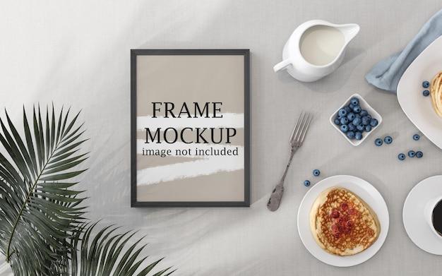 Moldura de pôster modelo na mesa ao lado da refeição