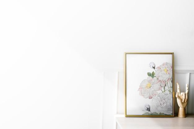Moldura dourada com manequim de mão em uma mesa branca