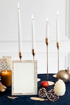 Moldura para fotos de natal em uma mesa com velas cônicas
