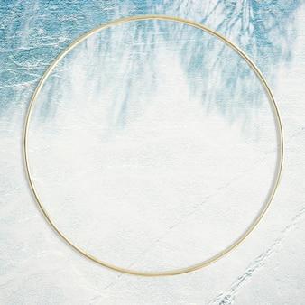 Moldura redonda dourada em um fundo frondoso e sombreado