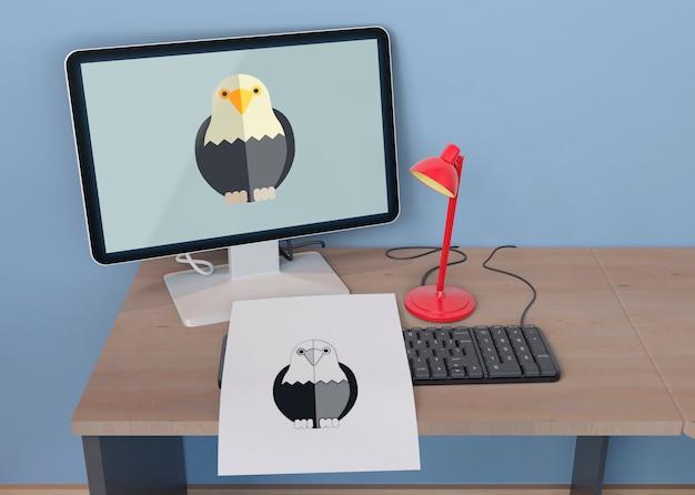 Monitor e folha com desenho de águia