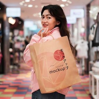 Mulher andando no shopping com sacola de compras média