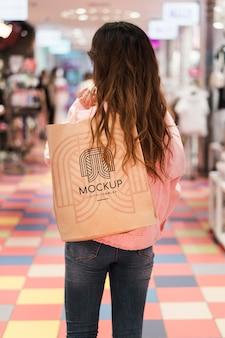 Mulher andando no shopping com uma sacola de compras por trás