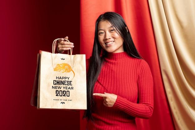Mulher apontando para bolsa com mensagem de feliz ano novo