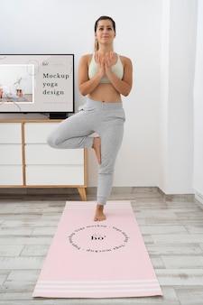 Mulher atlética fazendo ioga em casa