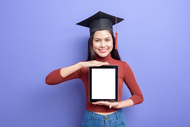 Mulher bonita no chapéu de formatura está segurando a maquete do tablet