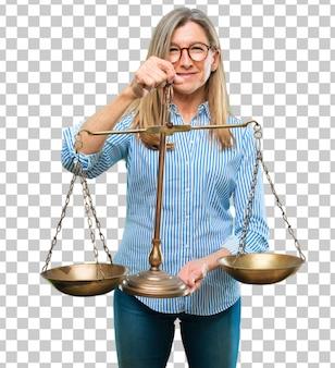 Mulher bonita sênior com um equilíbrio de justiça ou escala