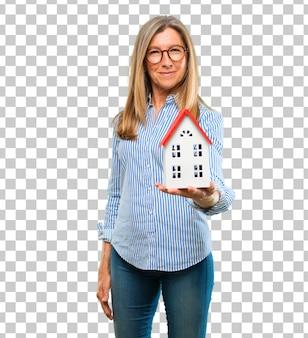 Mulher bonita sênior com um modelo de casa