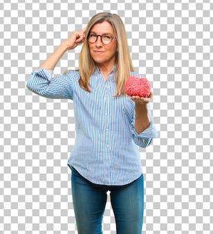 Mulher bonita sênior com um modelo de cérebro