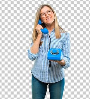 Mulher bonita sênior com um telefone vintage