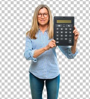 Mulher bonita sênior com uma calculadora