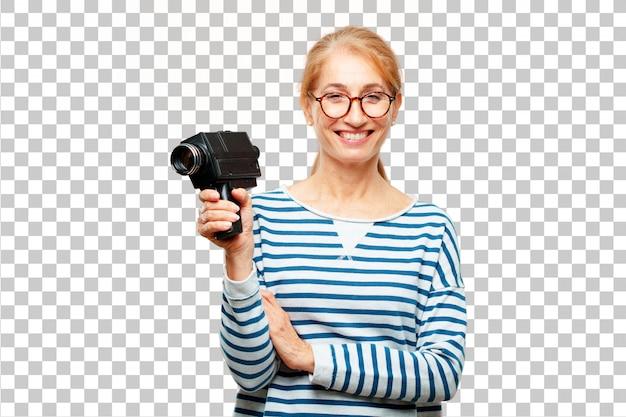 Mulher bonita sênior com uma câmera de cinema vintage