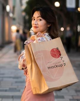 Mulher caminhando ao ar livre com uma sacola de compras