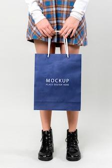Mulher carregando uma maquete de sacola de compras