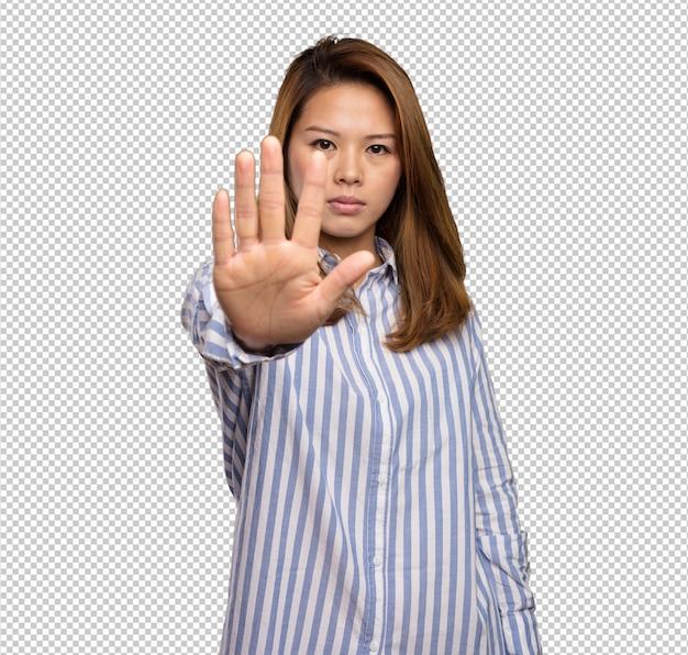 Mulher chinesa fazendo o gesto de parada