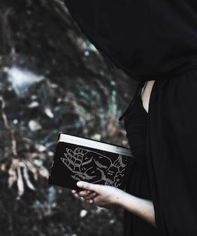 Mulher com capuz preto, lendo um livro de feitiços