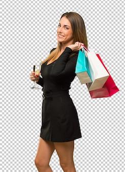 Mulher, com, champanhe, celebrando, novo ano, 2019, segurando, um, muitos, bolsas para compras