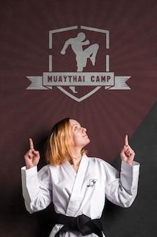 Mulher com faixa preta de karatê, apontando o logotipo da maquete