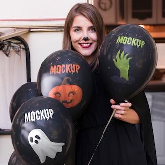 Mulher com fantasia de halloween segurando balões de referência