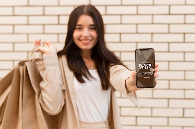 Mulher com maquete de smartphone preto sexta-feira