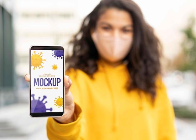 Mulher com máscara médica segurando uma maquete de smartphone