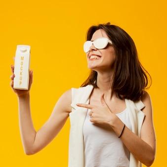 Mulher com óculos de sol, apontando para o leite