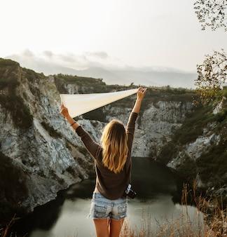 Mulher com os braços levantados e segurando bandeira na montanha