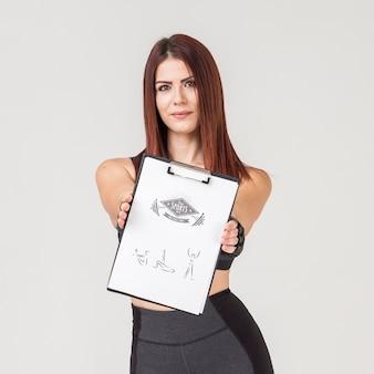 Mulher com roupas de ginástica, segurando o bloco de notas